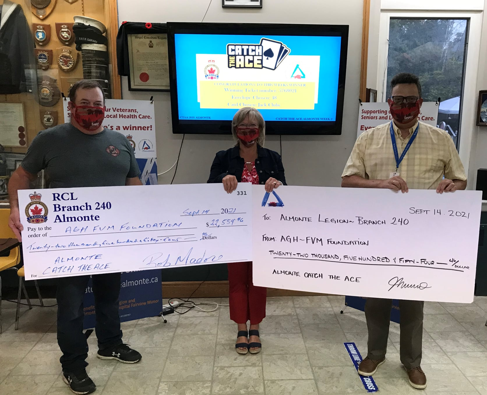three people holding large cheques for a presentation